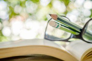 Close up of pencil , eyeglasses and open book on bokeh backgroun