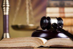 Mallet of the judge, justice scale, wooden desk background