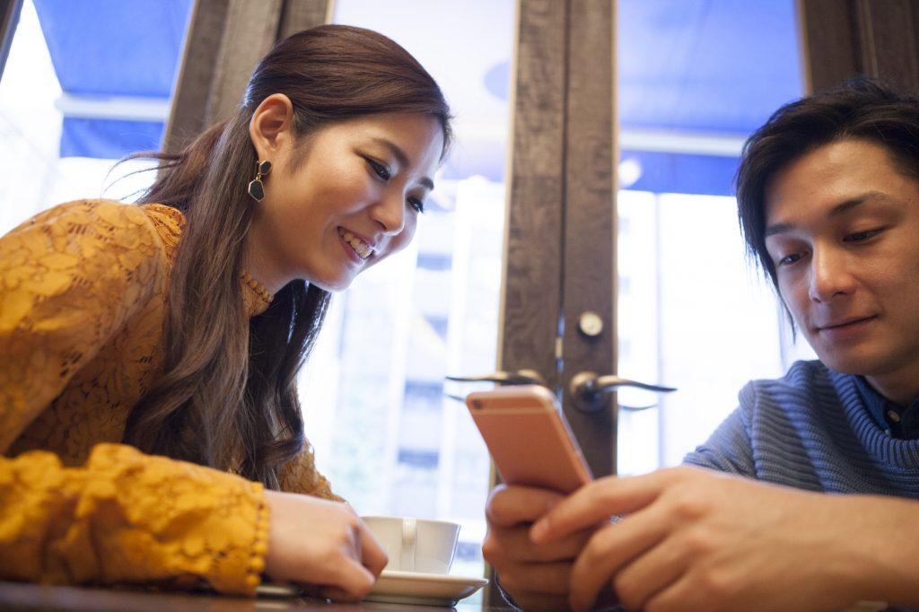 Young couple looking at a smart phone in a cafe