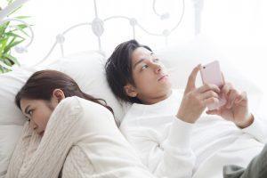 The man is looking at the smartphone in bed